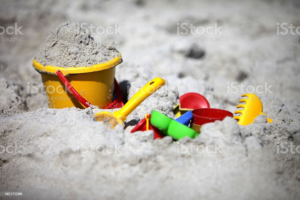 A close-up of a bucket and shovel in the sand of a beach stock photo