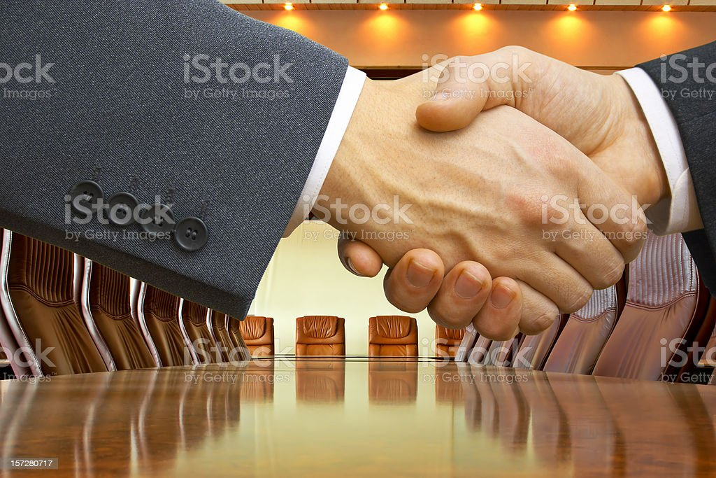 Close-up of a business deal handshake at an empty table royalty-free stock photo
