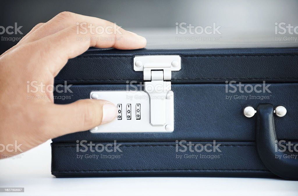 Closeup of a business hand opening briefcase combination lock royalty-free stock photo