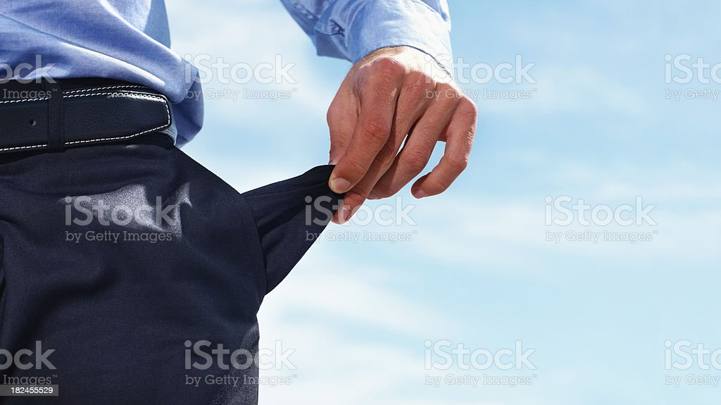 Closeup of a business man pulling out empty pocket stock photo