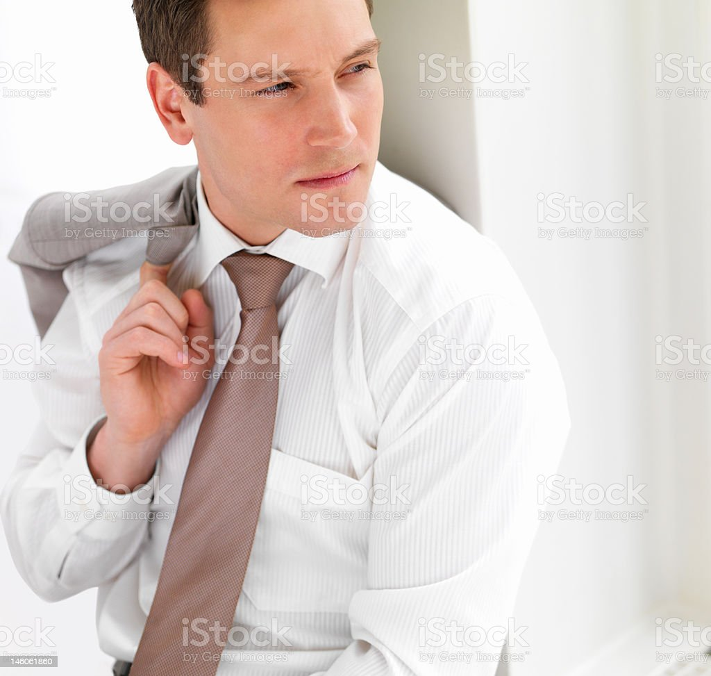 Close-up of a businessman sitting on floor and looking away royalty-free stock photo