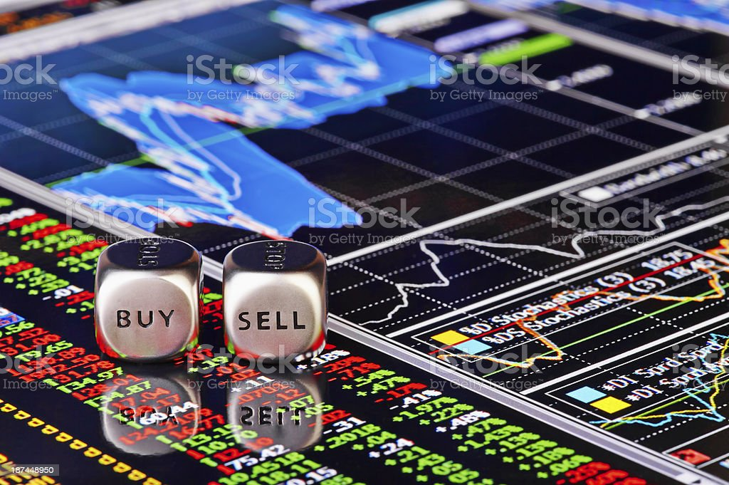 Close-up of a buy and sell roll of dice over trader's chart stock photo