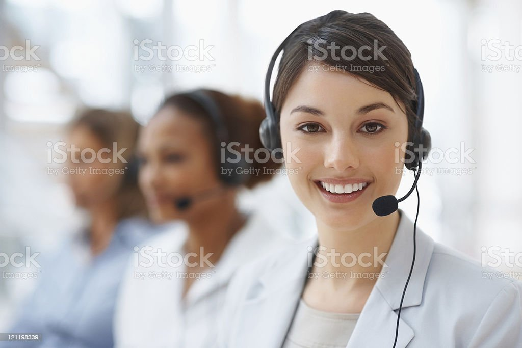 Closeup of a call center employee with headset at workplace stock photo