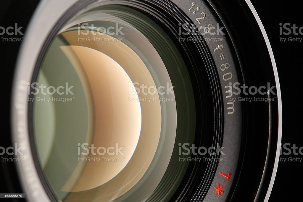 A close-up of a camera lens on a black background stock photo