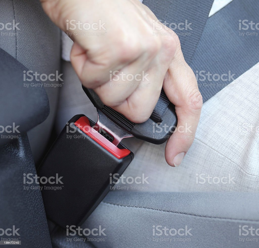Closeup of a car seat buckle being locked in stock photo