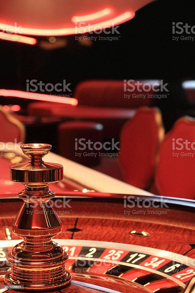 Close-up of a casino roulette table with blurred chairs royalty-free stock photo