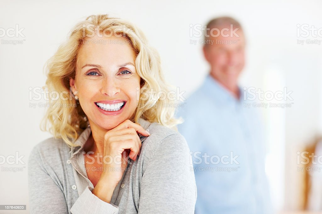 Close-up of a cheerful mature woman with man in background stock photo