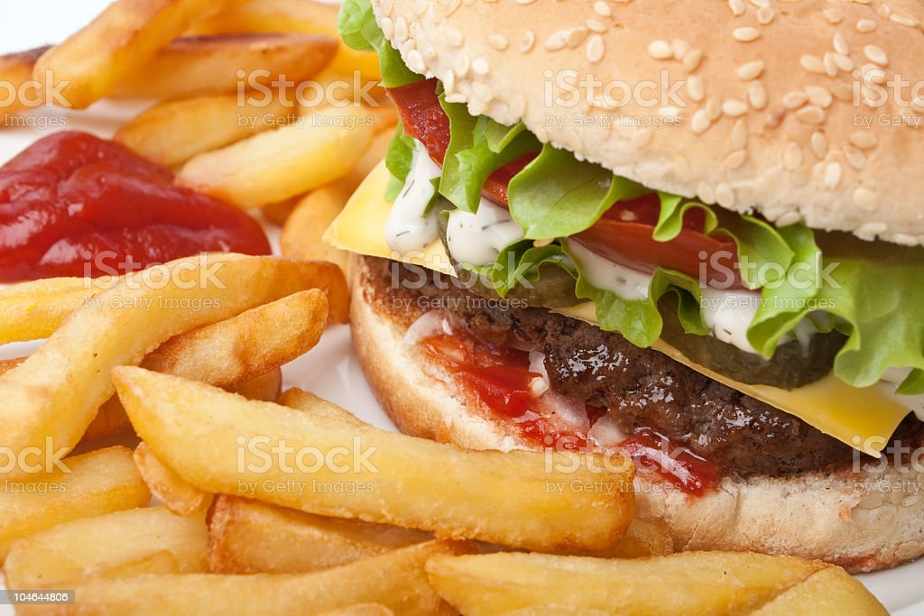 A close-up of a cheeseburger with fries and ketchup stock photo