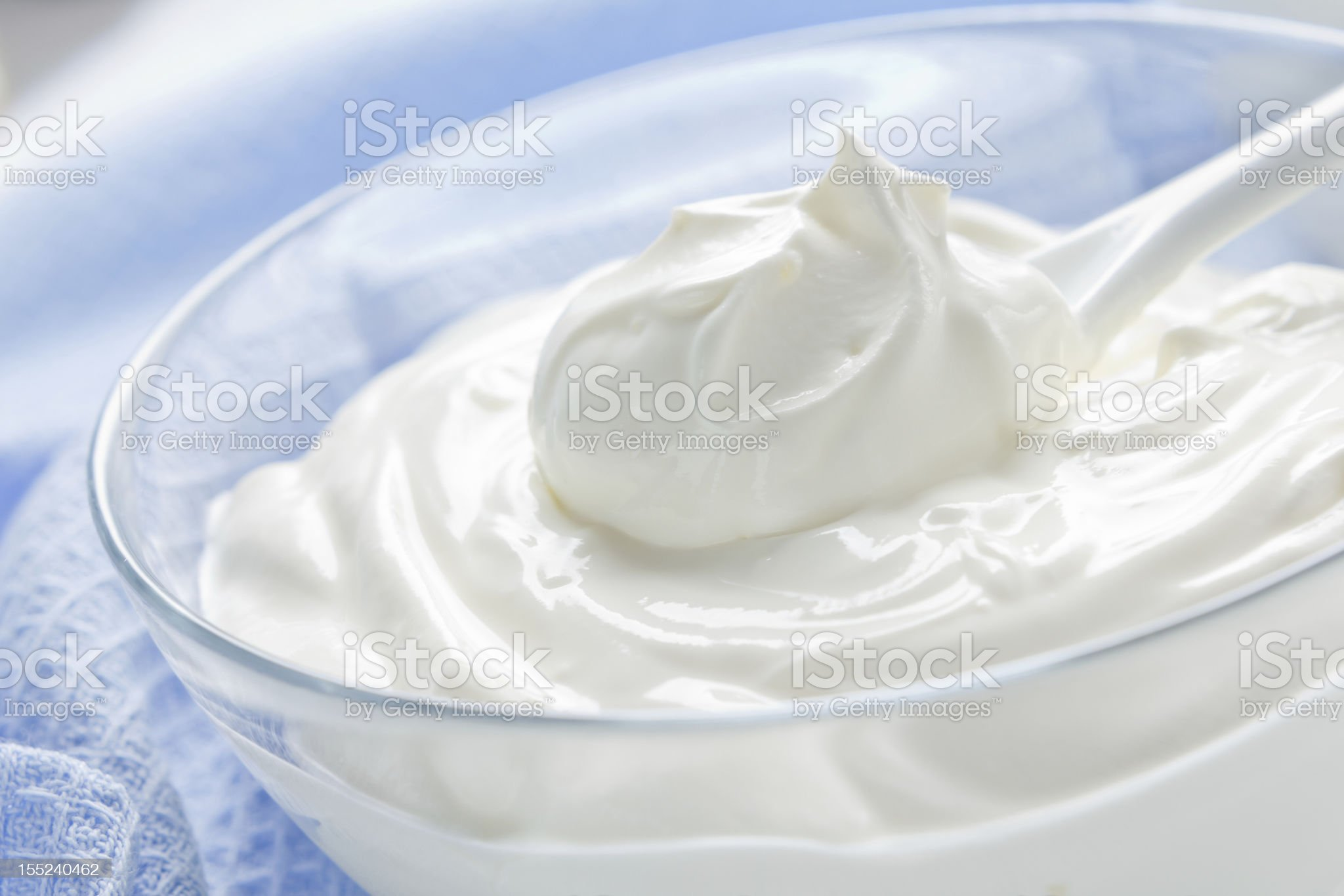 Close-up of a clear bowl of sour cream with plastic spoon royalty-free stock photo