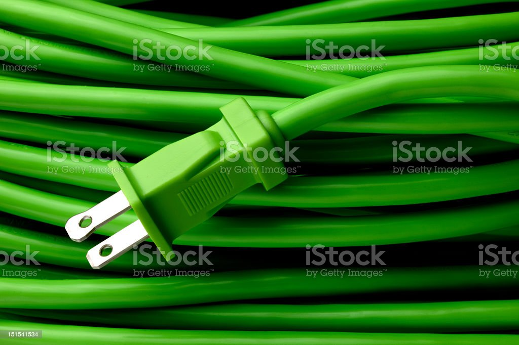 Close-up of a coiled up green extension cord and plug royalty-free stock photo