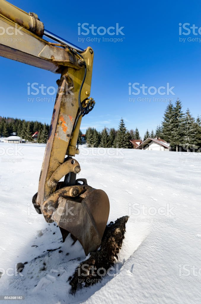 Close-up of a construction site excavator working on winter snow stock photo