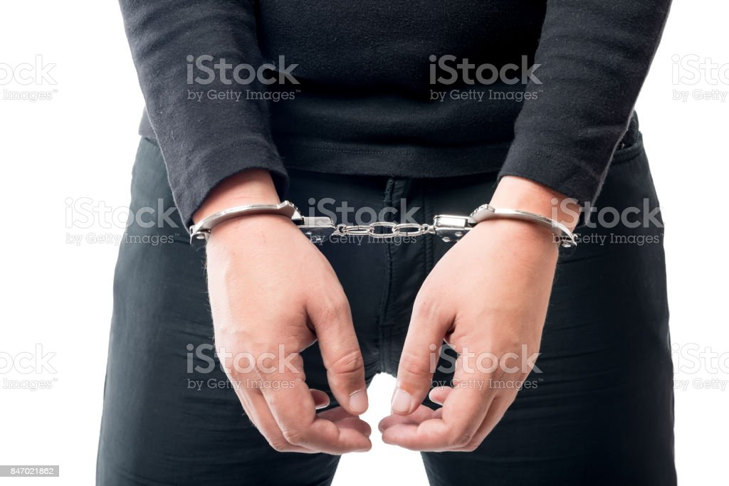 Close-up of a criminal hand in handcuffs stock photo