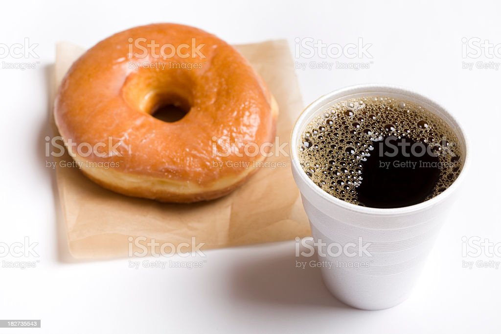 a glazed donut next to a cup of coffee in a styrofoam cup