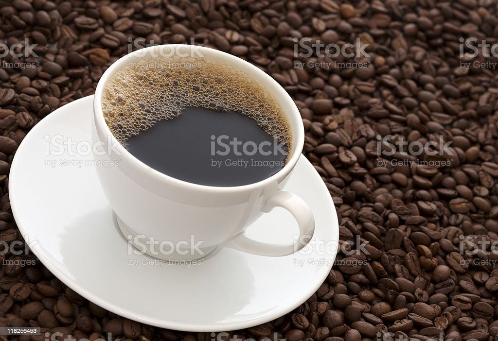 Close-up of a cup of black coffee on a layer of coffee beans stock photo