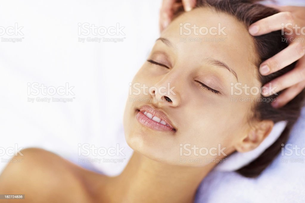 Closeup of a cute woman receiving head massage at spa royalty-free stock photo