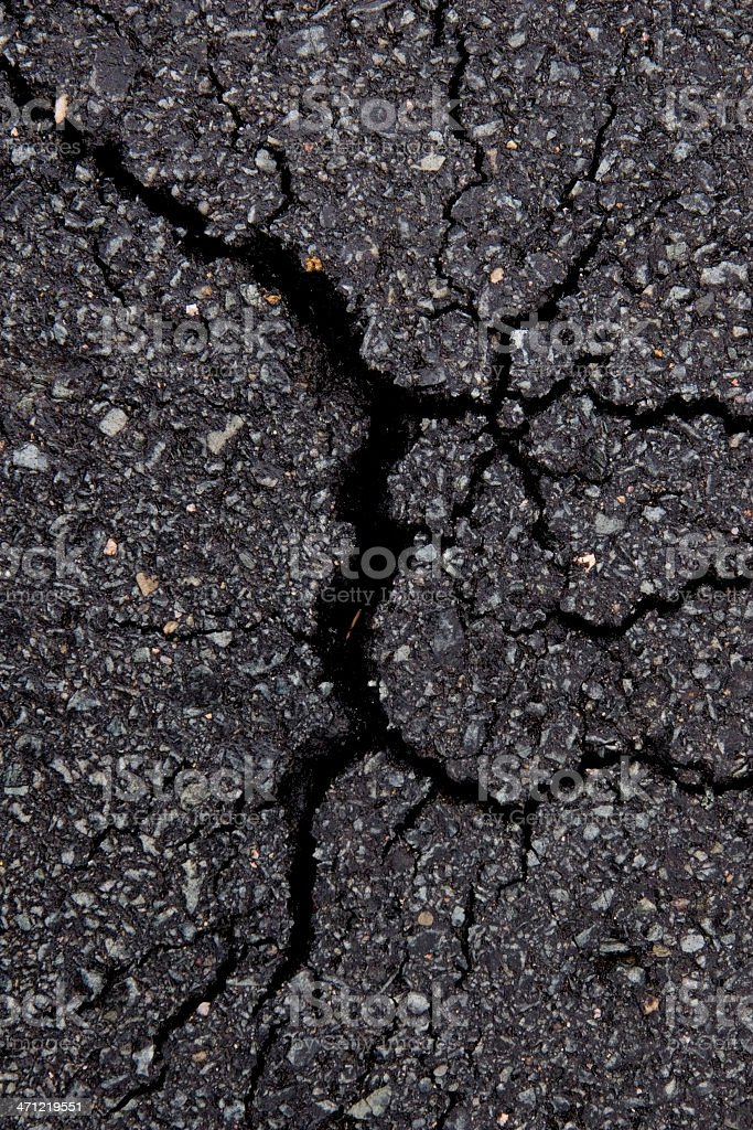 Close-up of a dark gray cracked asphalt pavement stock photo