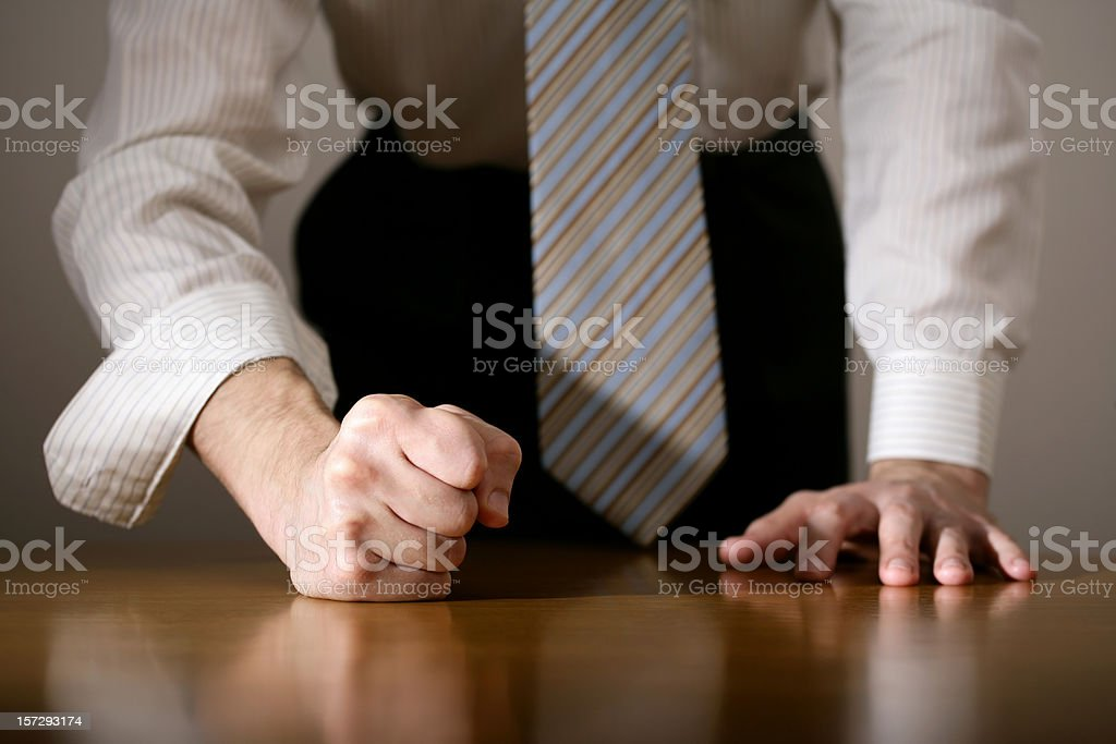 Close-up of a determined man with his fist on the table stock photo