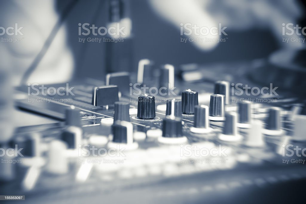 Close-up of a DJ hand on turntable, blue toned royalty-free stock photo