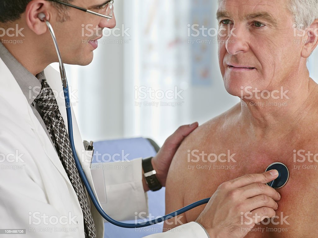 Close-up of a doctor examining senior man with stethoscope royalty-free stock photo