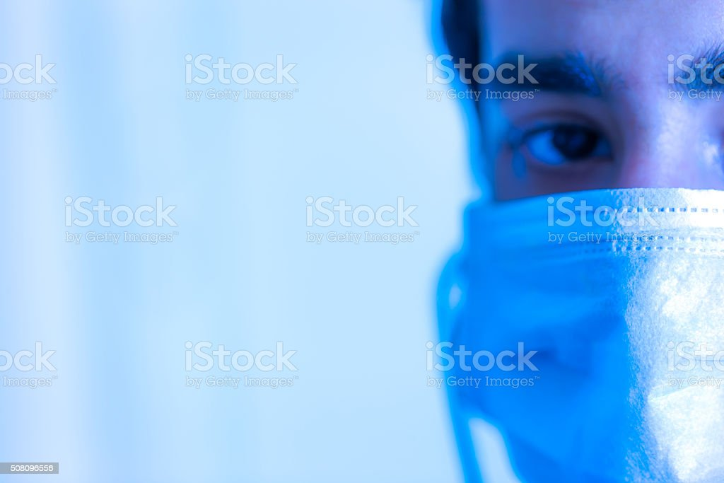 Extreme Closeup of a doctor\'s face with a protective mask with a copy...