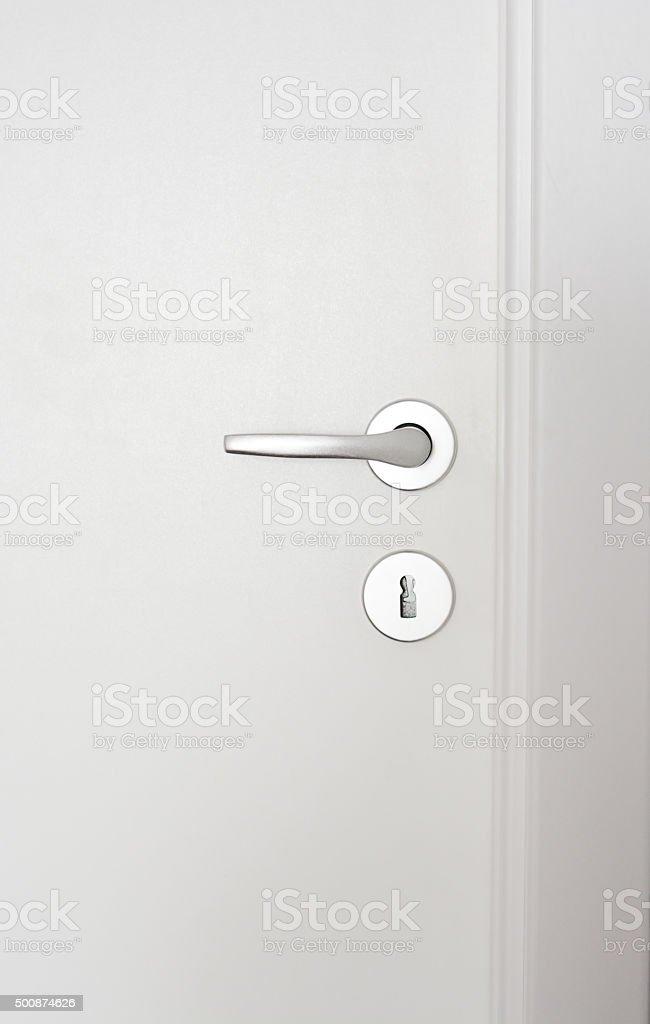 Close-up of a doorknob on white wood door stock photo