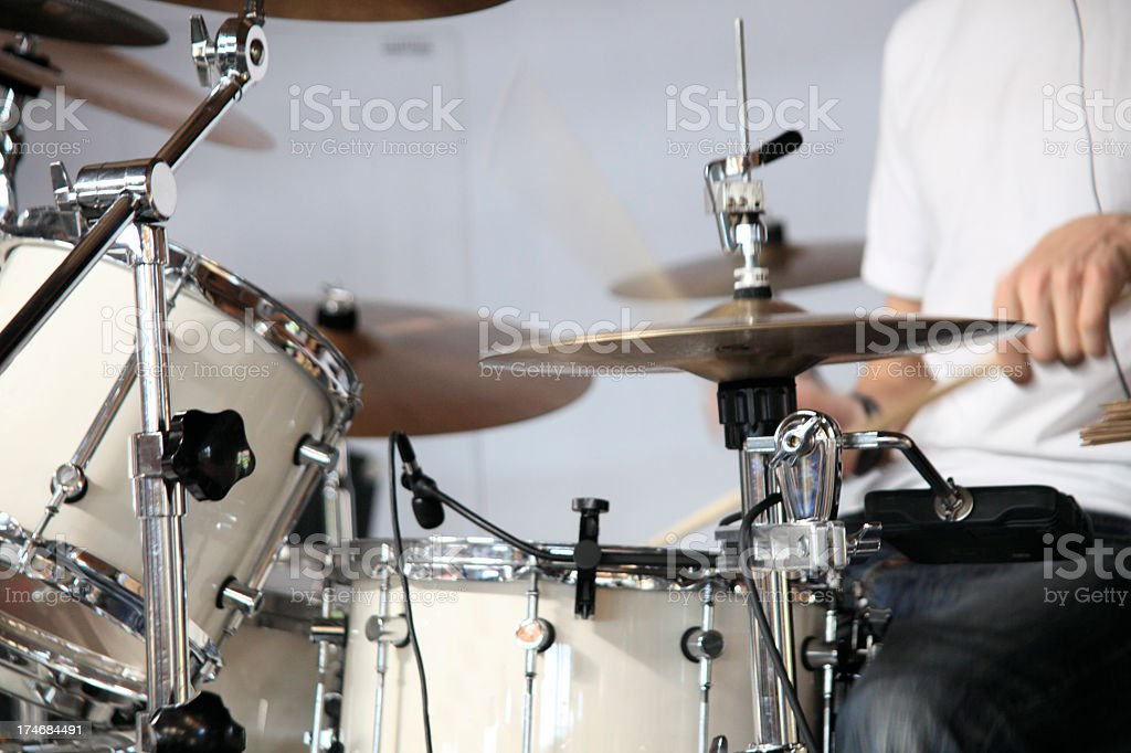 Close-up of a drum kit being played by a man in jeans royalty-free stock photo