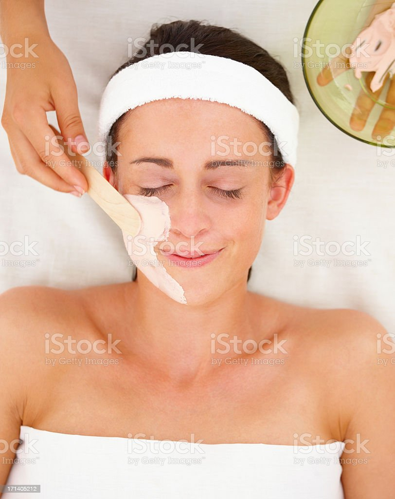 Closeup of a facial mask treatment being applied on a young pretty girl stock photo