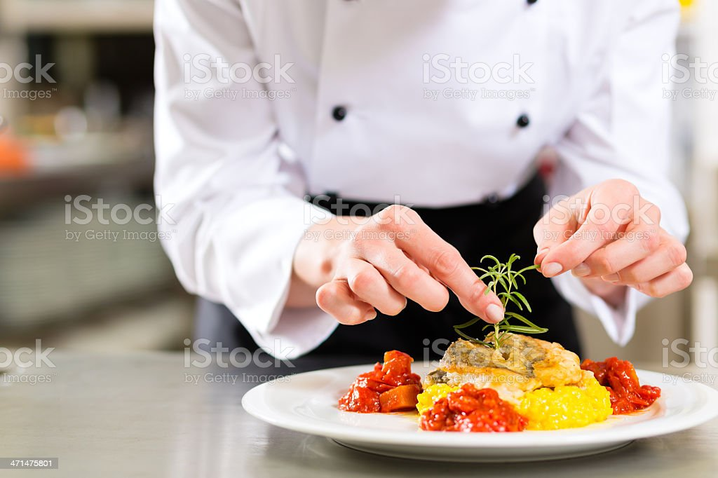 Close-up of a female chef putting final touches on plate stock photo