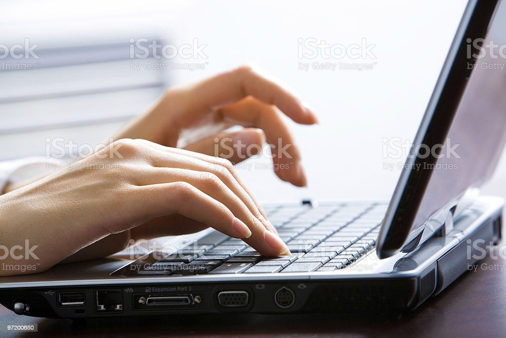 Close-up of a female's hands typing on a laptop keyboard royalty-free stock photo