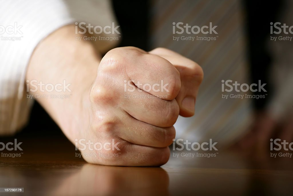 Close-up of a fist resting on a wooden surface stock photo