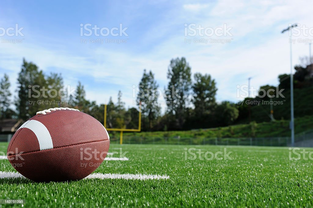 Close-up of a football on a field with view of the goalpost stock photo