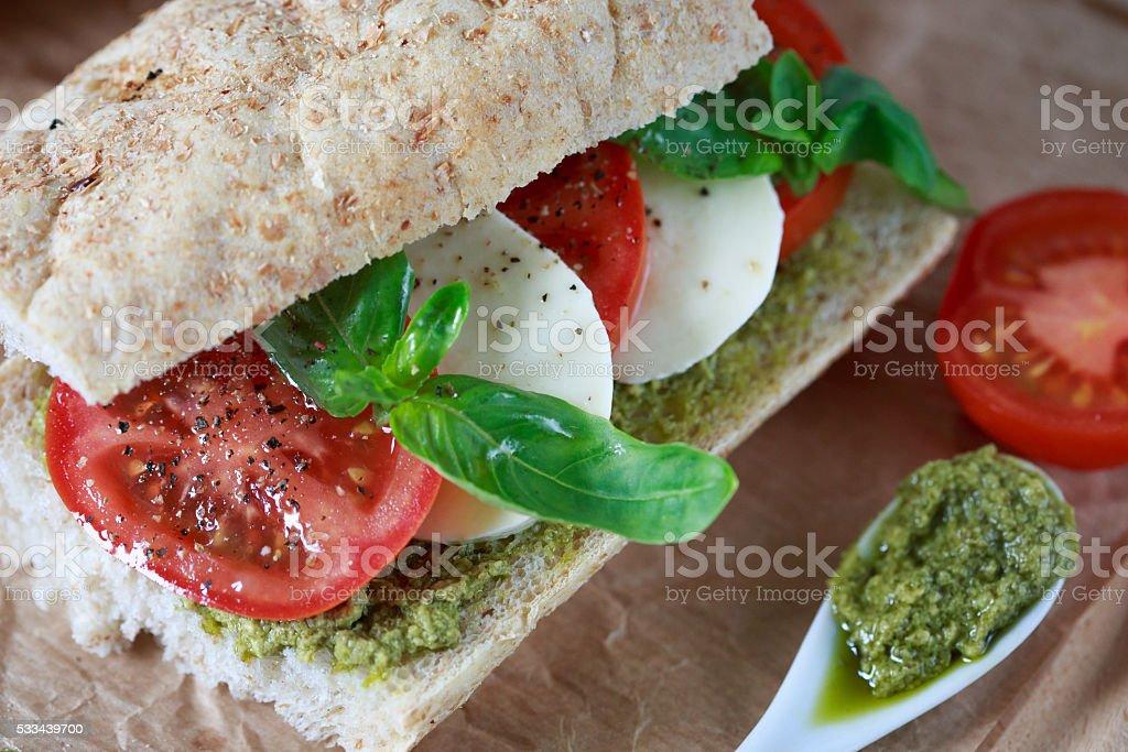 Closeup of a fresh sandwich with mozzarella, tomatoes, pesto stock photo