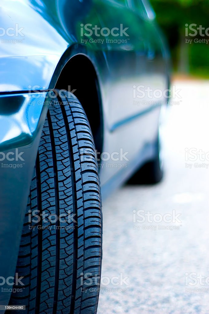 Close-up of a front tire that is pointing outward on a car stock photo