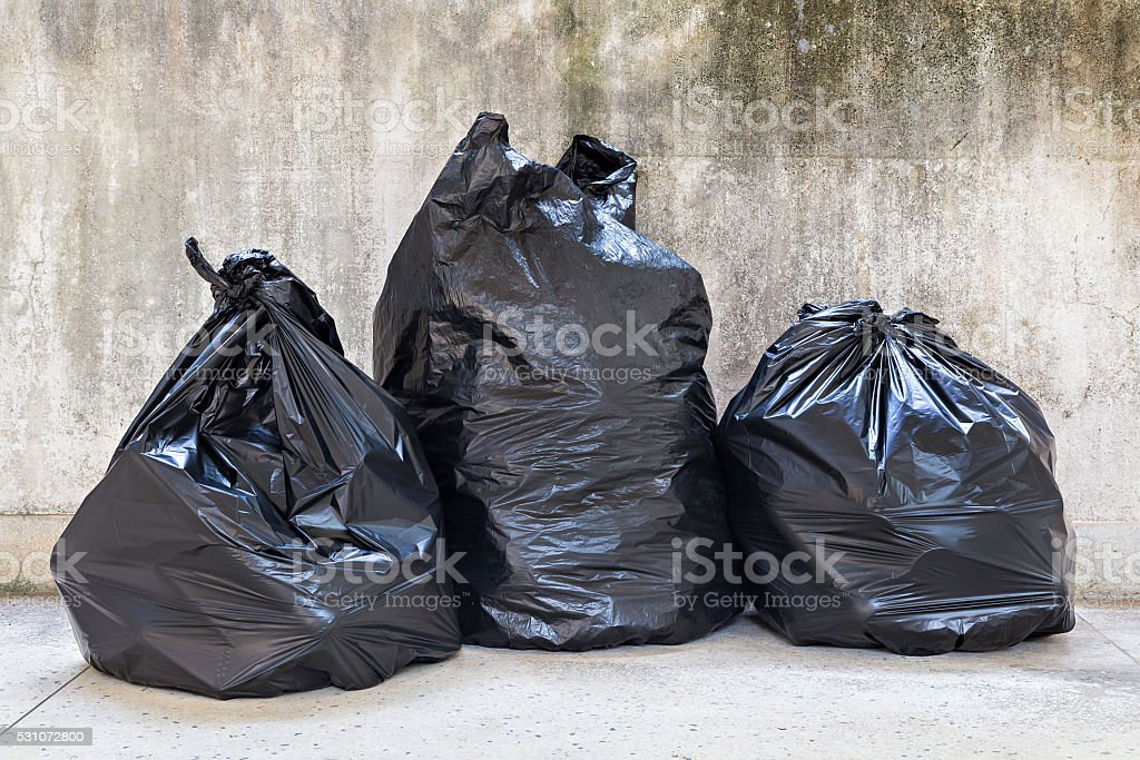 close-up of a full garbage bags on floor stock photo