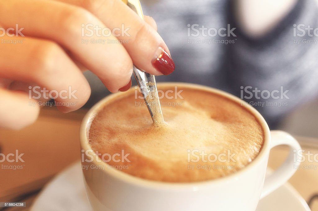 Closeup of a girl stirs the coffee with crema stock photo