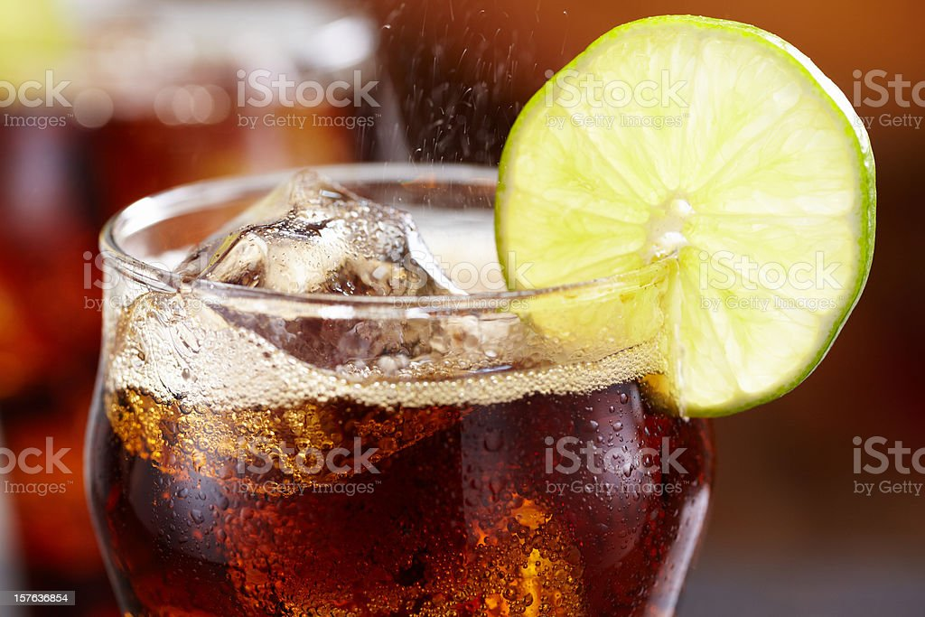 Close-up of a glass of cola with ice and lemon garnish royalty-free stock photo