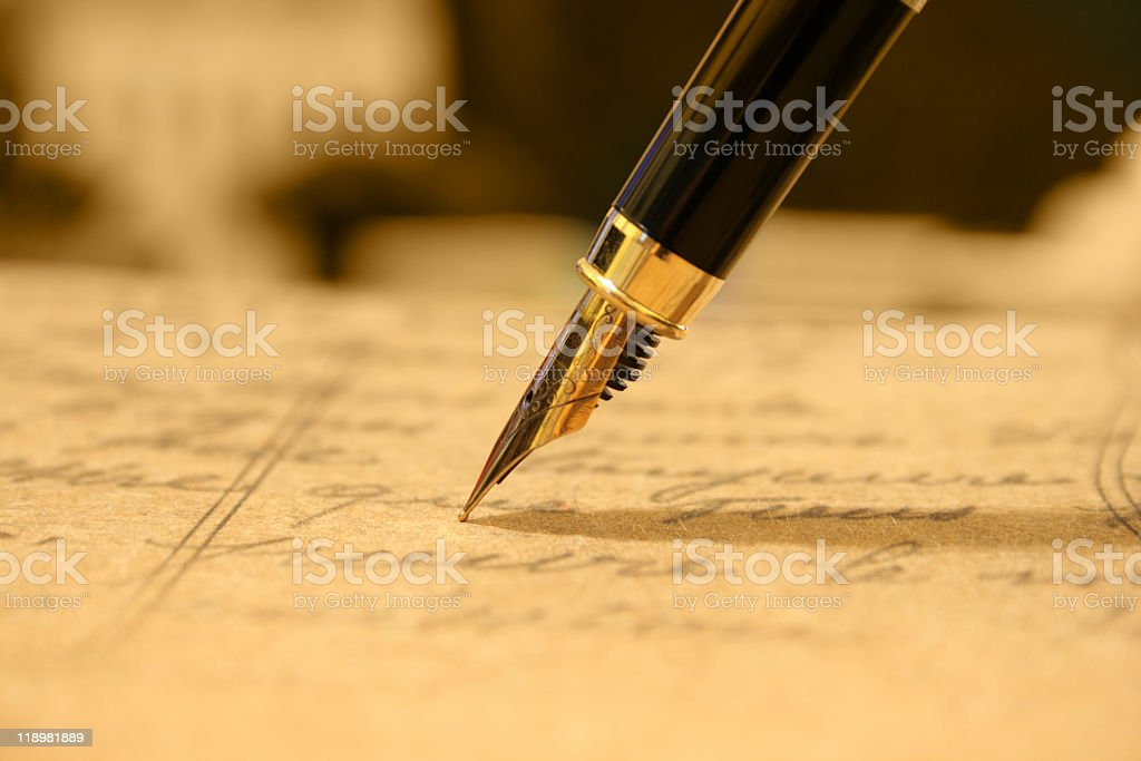 Close-up of a golden fountain pen writing stock photo