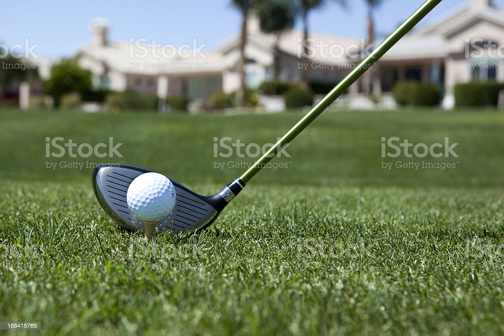 Close-up of a golf ball about to be hit in a field stock photo