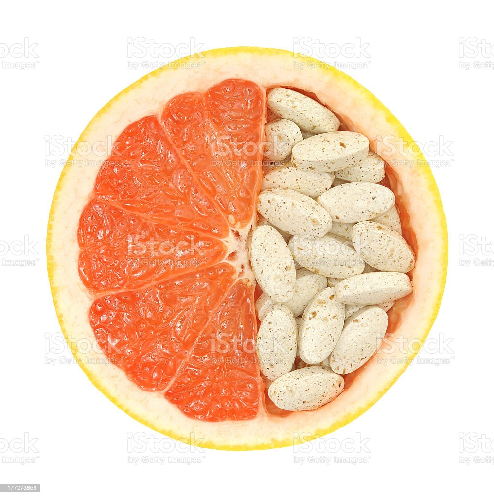 Close-up of a grapefruit halfway filled with pills stock photo