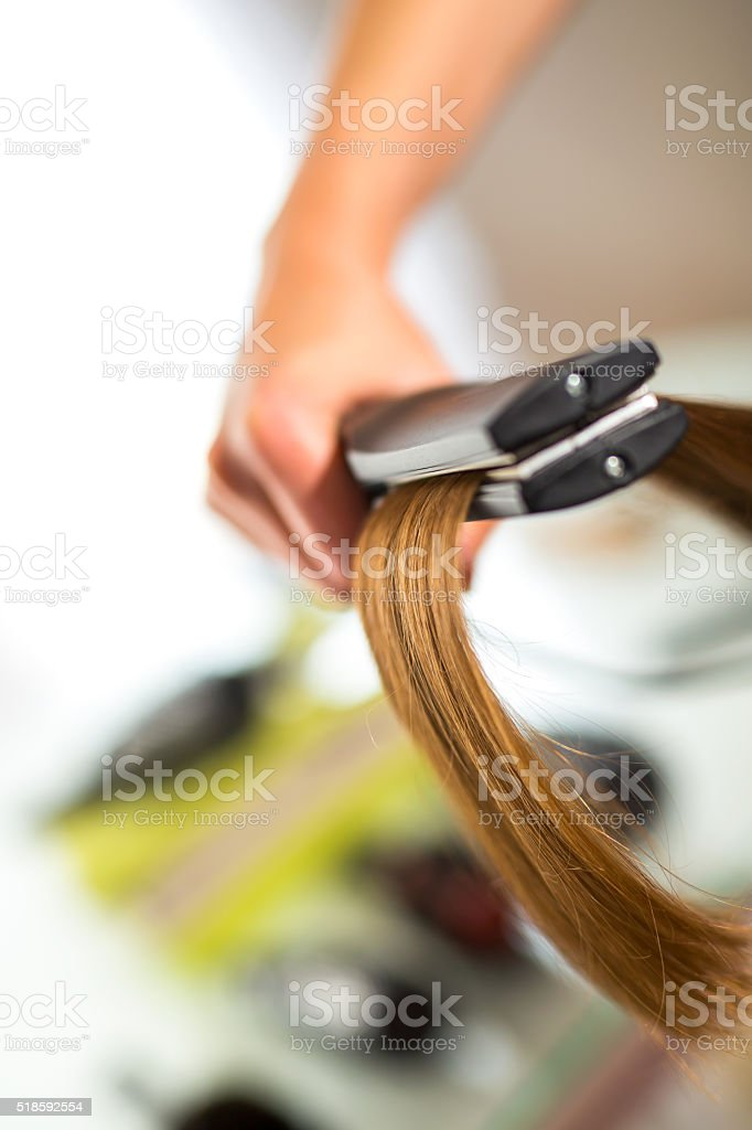 Close-up of a hairdresser straightening long blonde hair with ha stock photo