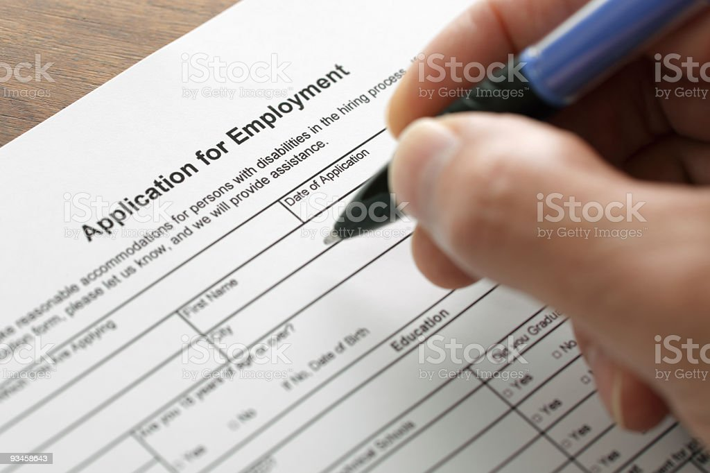 Close-up of a hand filling out a job application stock photo