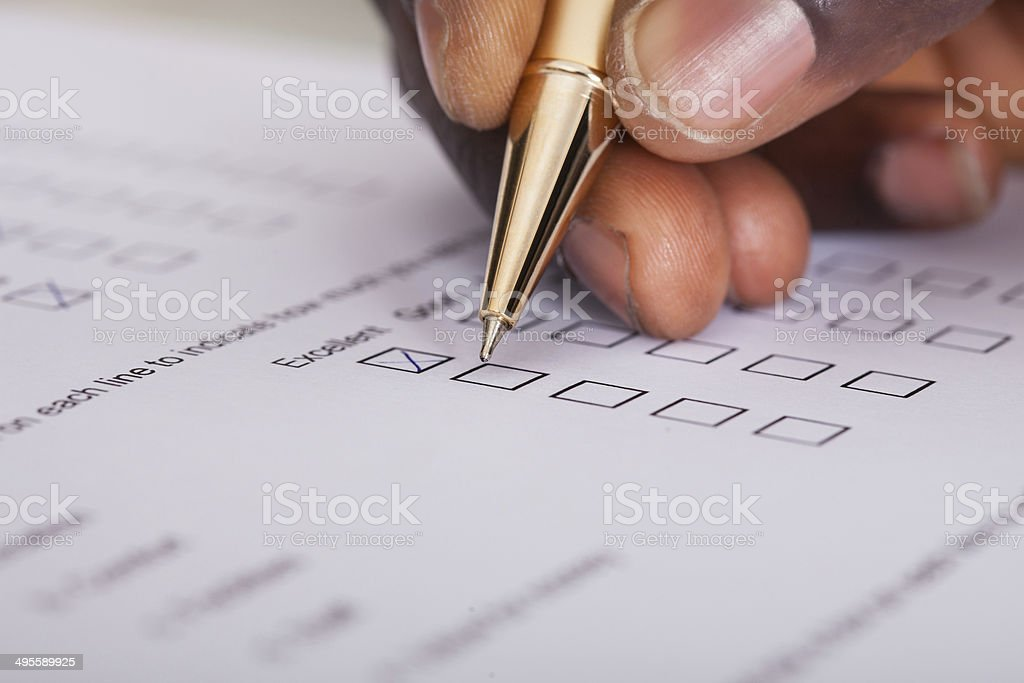 Close-up of a hand filling out a survey form stock photo