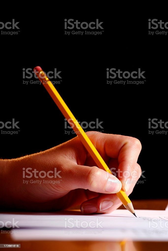 Close-up of a hand holding a pencil writing on document stock photo