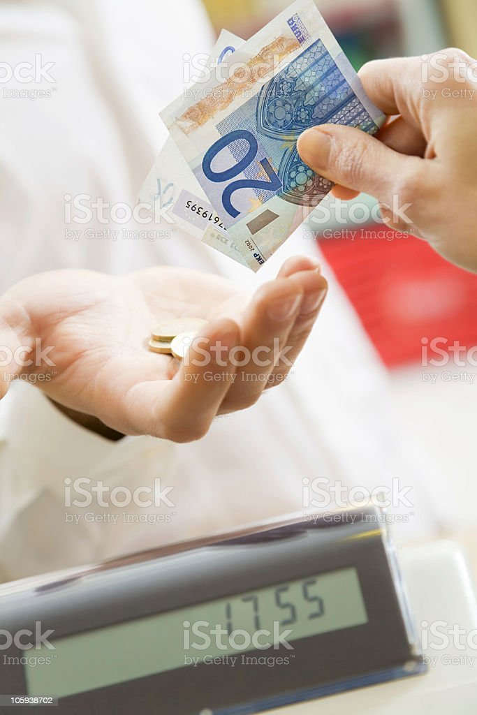 Closeup of a hand over register accepting money from a sale stock photo