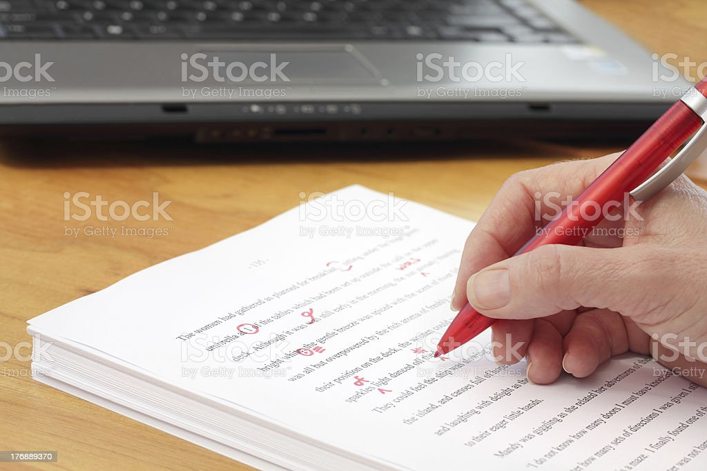 Close-up of a hand proofreading a manuscript with a red pen stock photo