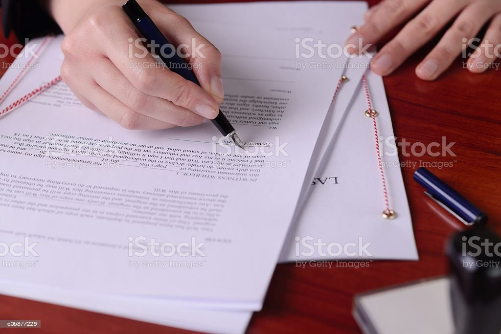 Closeup of a hand signing a last will by  pen. stock photo