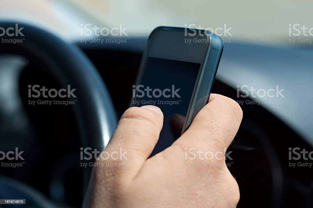 Close-up of a hand texting on a cell phone while driving royalty-free stock photo