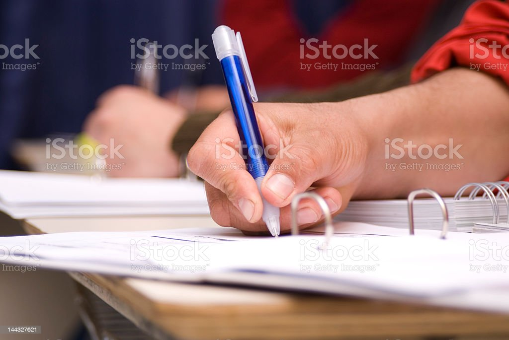 Close-up of a hand that is writing on paper with a blue pen stock photo
