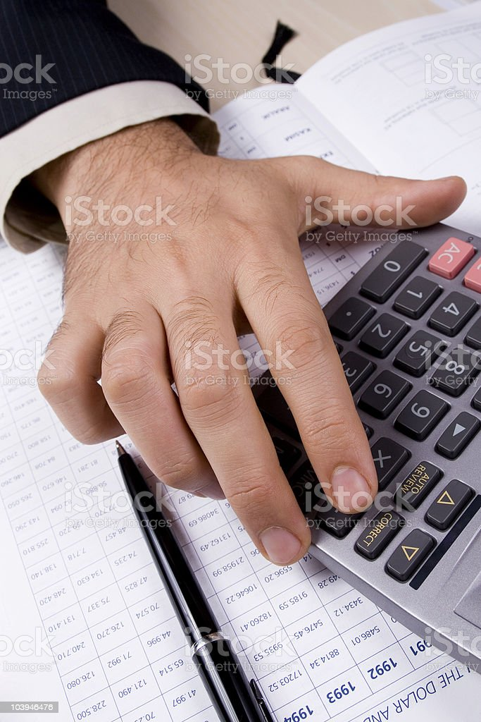 Close-up of a hand using a calculator next to a pen royalty-free stock photo