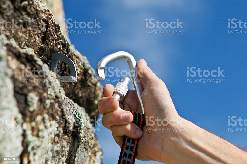 Close-up of a hand using a carbine and hook to climb a wall stock photo